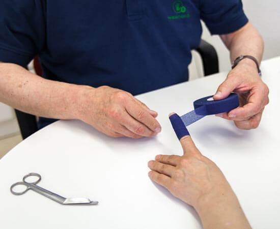 Ein Tapeverband wird von einem Handchirurgen um einen Finger gewickelt